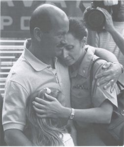 Photograph of Commander Barbara Vernoski hugging her husband and daughter before boarding the USNS Comfort in 1990.
