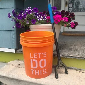 Photograph of orange trash bucket and trash picker on porch step.