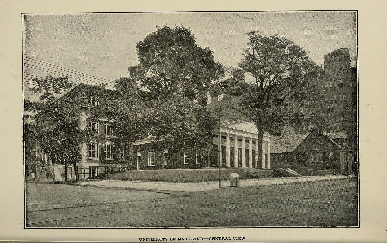 Photograph of UMB Campus circa 1920, has two trees and three buildings.