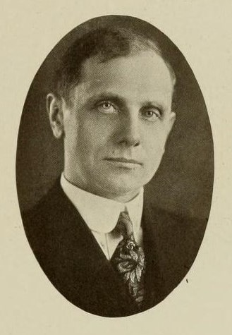 Black and white photograph of a man in a suit and tie