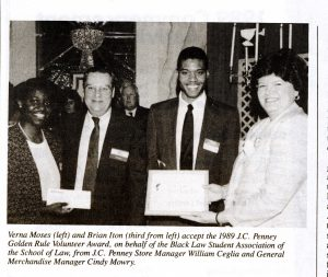 Black and white newspaper clipping of four people standing and smiling, to the left is a man presenting a check to a woman; to the right is a woman presenting an award to a man