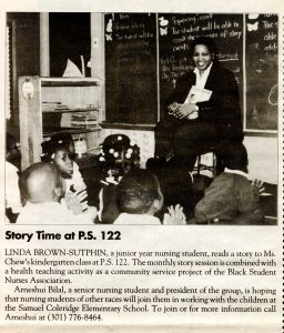 Black and white newspaper clipping of a student sitting in the front of a classroom reading a book to a group of students sitting on the floor.