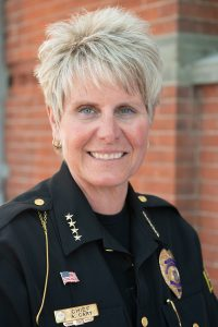 Color photograph of a woman with short blond hair in a police uniform, the woman is smiling