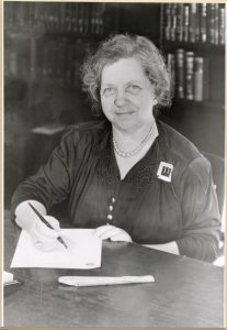 Photograph of a woman with curly hair sitting at a table with a pen and paper, she is smilin at the camera