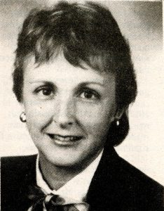 Black and white photograph of a woman, she has short hair and is smiling at the camera