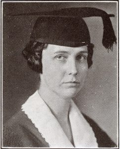 Black and white photograph of a woman with a graduation cap and tassle.