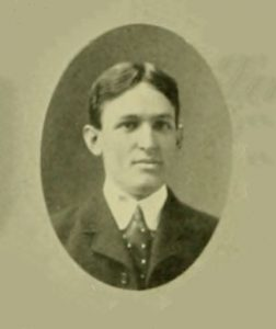 Black and white yearbook photograph of man in jacket.