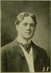 Black and white yearbook photograph of a man in a jacket.