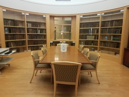Photograph of a room in the HSHSL Historical Collections, in center of room is a conference table with eight chairs around it, around the room is built in book shelves.