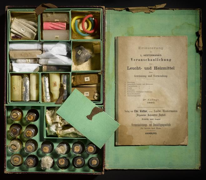 Photograph of an 19th century chemistry set, complete with chemical viles in compartments and a book with instructions on using it