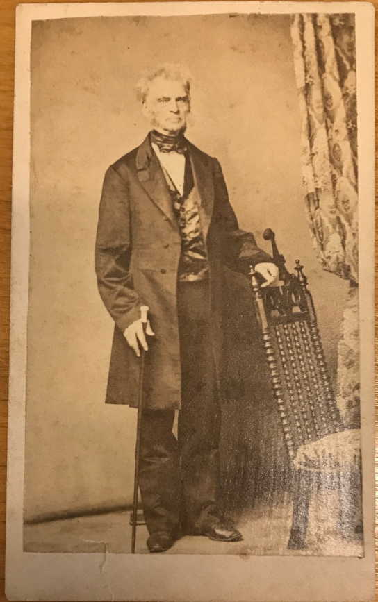 Sephia photograph of an older man leaning against a chair, he is wearing a long coat, bow tie, and vest.