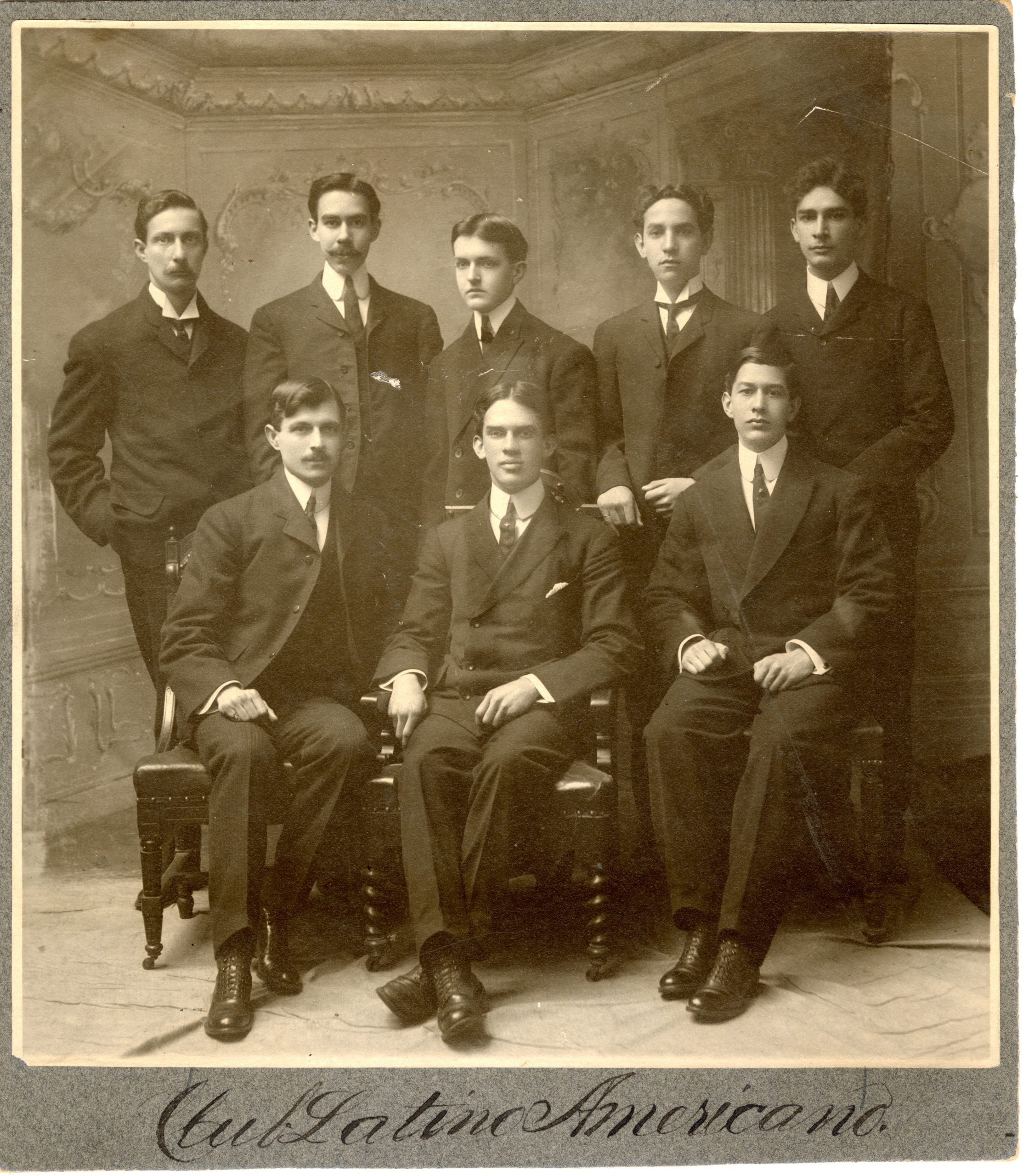 Sepia photograph of a group of 8 men, five standing behind three seated in chairs. Caption on the bottom handwritten says Club Latino Americano.