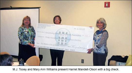 M.J. Tooey and Mary Ann Williams present Harriet Mandell-Olson with a big check.