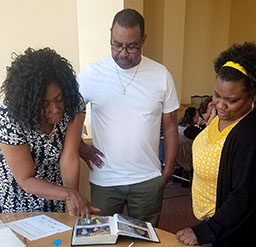 HS/HSL staff members Charlene Matthews, Patrick Williams and Shanell Stephens view old photos of the HS/HSL